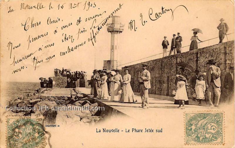 Carte postale ancienne datée du 16 août1903, légendée, la Nouvelle, Le phare jetée Sud. On aperçoit le phare, et quelques groupes de personnes endimanchées.