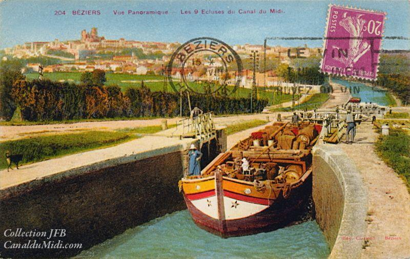 Carte postale ancienne colorisée légendée : Béziers,     vue panoramique, les 9 écluses et le Canal du Midi. Une péniche à     la cargaison indéfinie se dirige vers l'amont (vers nous). En arrière     plan, on peut voir Béziers et sa cathédrale. La flamme du cachet de     la poste fait de la publicité : il est écrit : Buvez du vin !