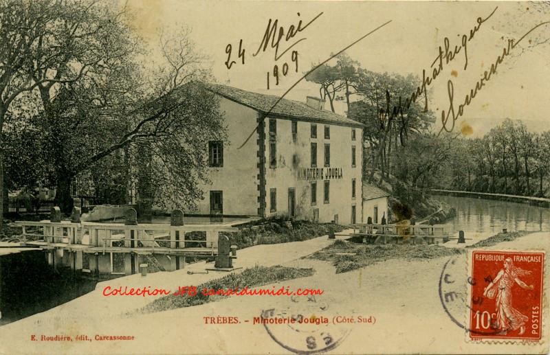 Carte postale ancienne, légendée : Trèbes Minoterie     Jougla (Côté Sud), datée du 24 mai 1909. On aperçoit     à gauche, le vantail amont de l'écluse, puis le bâtiment de     la minoterie et le vantail aval de l'écluse. Ensuite, le canal du midi décrit     une courbe vers la gauche pour disparaitre derrière le bâtiment.
