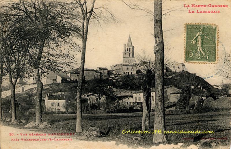 Carte postale ancienne, légendée : La Haute-Garonne - Le Lauragais -      Vue générale d'Avignonet près     Villefranche de Lauragais. On aperçoit une partie de la route, et quatre     arbres qui la bordent. Plus loin dans un pré, un mûrier. Le cœur     du village est situé sur une petite colline et l'église domine. Au     pied de la colline, quelques maisons.