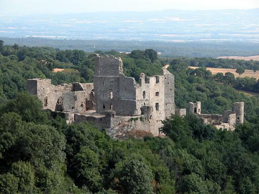Belle vue d'ensemble du château de Saissac. Il semble émerger de la forêt. Dans le lointain, la plaine de l'Aude et le Seuil de Naurouze